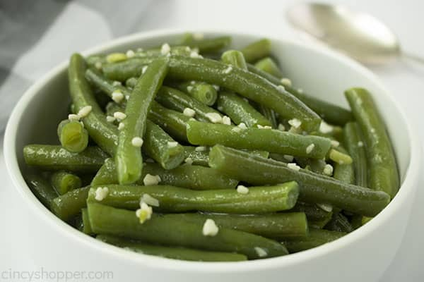 Sideways shot of white bowl filled with fresh garlic butter green beans