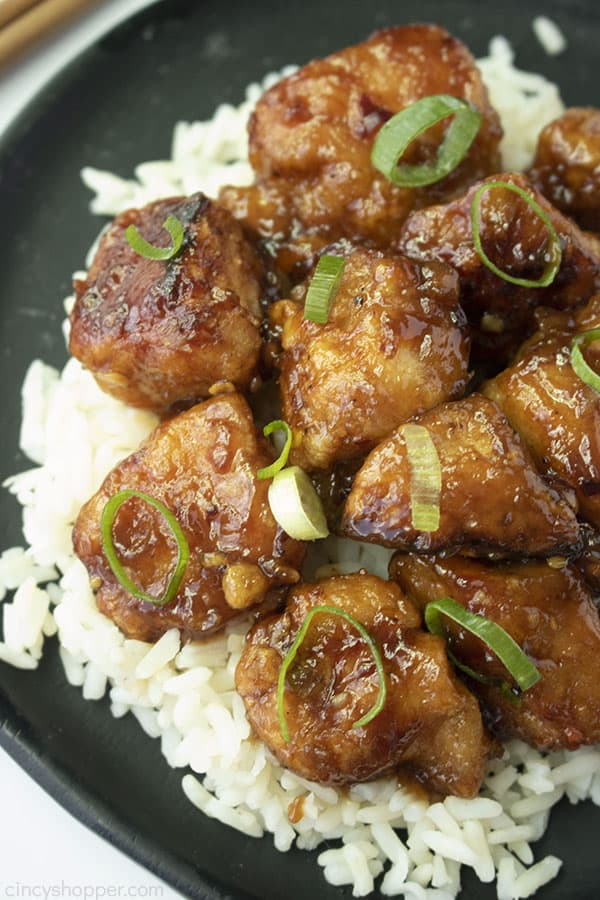 General Tso's Chicken over rice on a black plate.