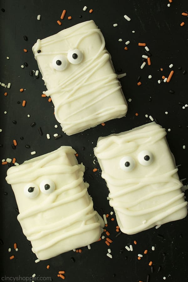 Mummy Krispie Treats on a black background with orange and white sprinkles.