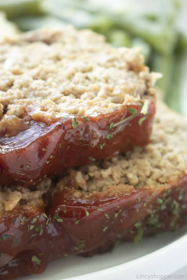 2 pieces of classic meatloaf on a white plate and green beans in the background.