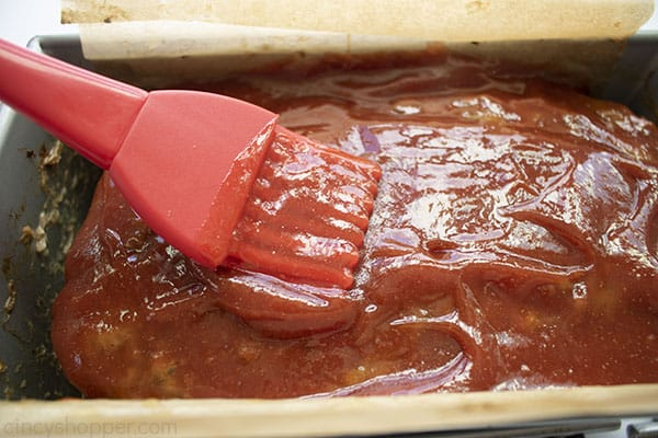 Basting brush with tangy ketchup sauce on top of meatloaf in a pan.