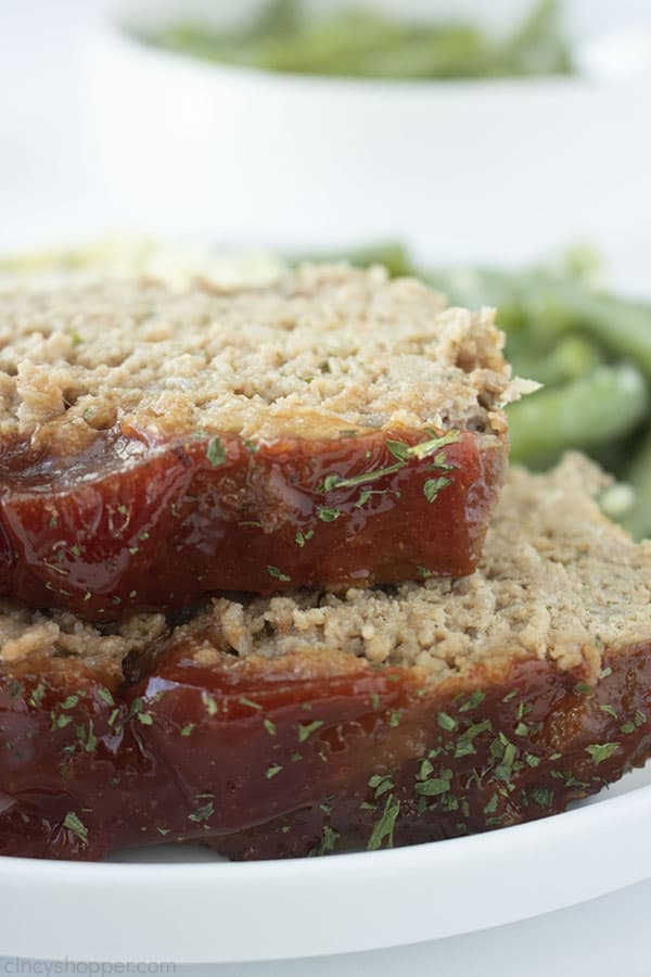 Stack with two pieces of easy meatloaf on a white plate, includes green beans.