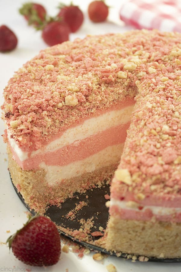 sliced pink and white strawberry crunch cheesecake with fresh strawberries