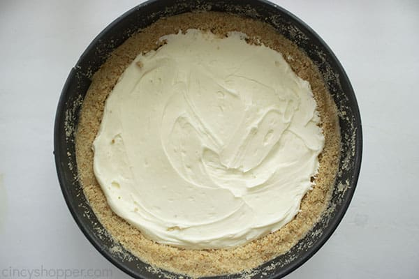 first layer of the cream cheese filling on top of the cheesecake crust in a large pie pan