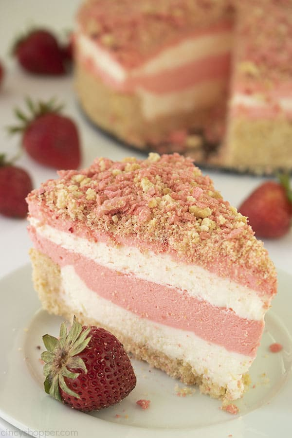 single slice of strawberry crunch cheesecake on a white plate