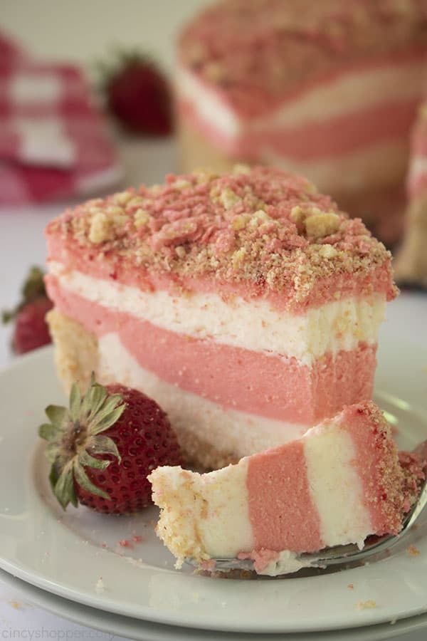 single bite of no-bake strawberry crunch cheesecake with a slice in the background