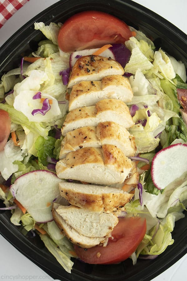 Sliced Chicken breasts on a green salad with black dish