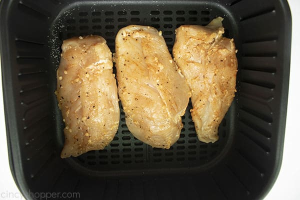 Uncooked and seasoned chicken breasts in a air fryer basket