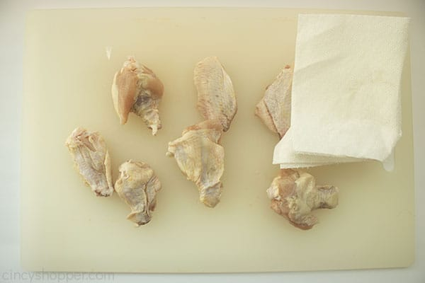 Chicken wings on a white cutting board with paper towel to pat dry
