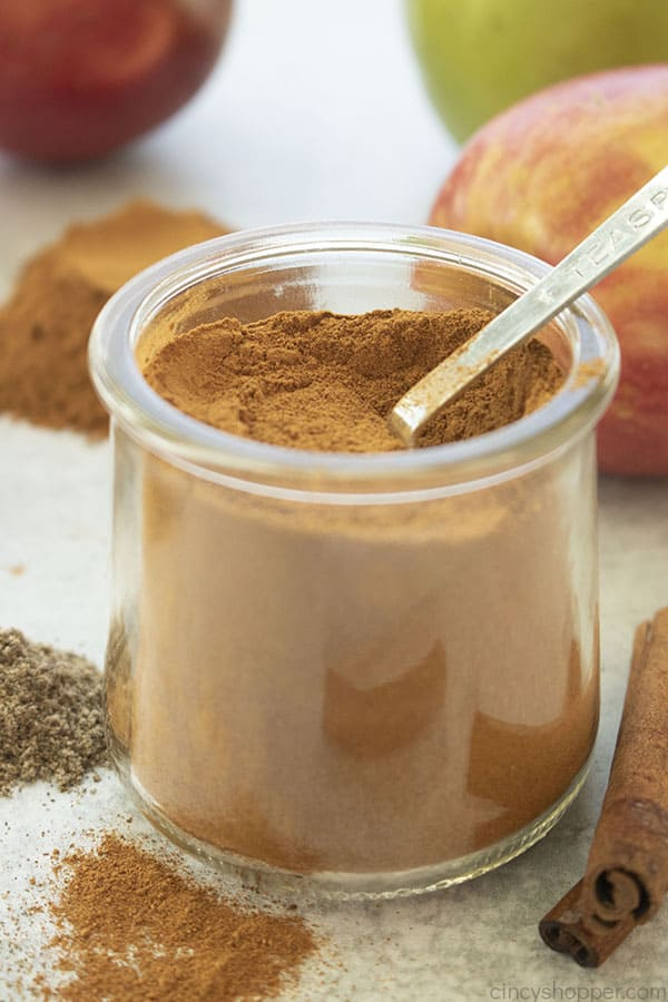 Apple pie spice in a clear jar with a teaspoon apples in the background
