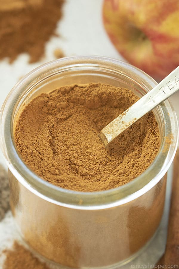 Overhead closeup of Apple Pie Spice mix in a clear jar with spoon. Spices and apple in the background
