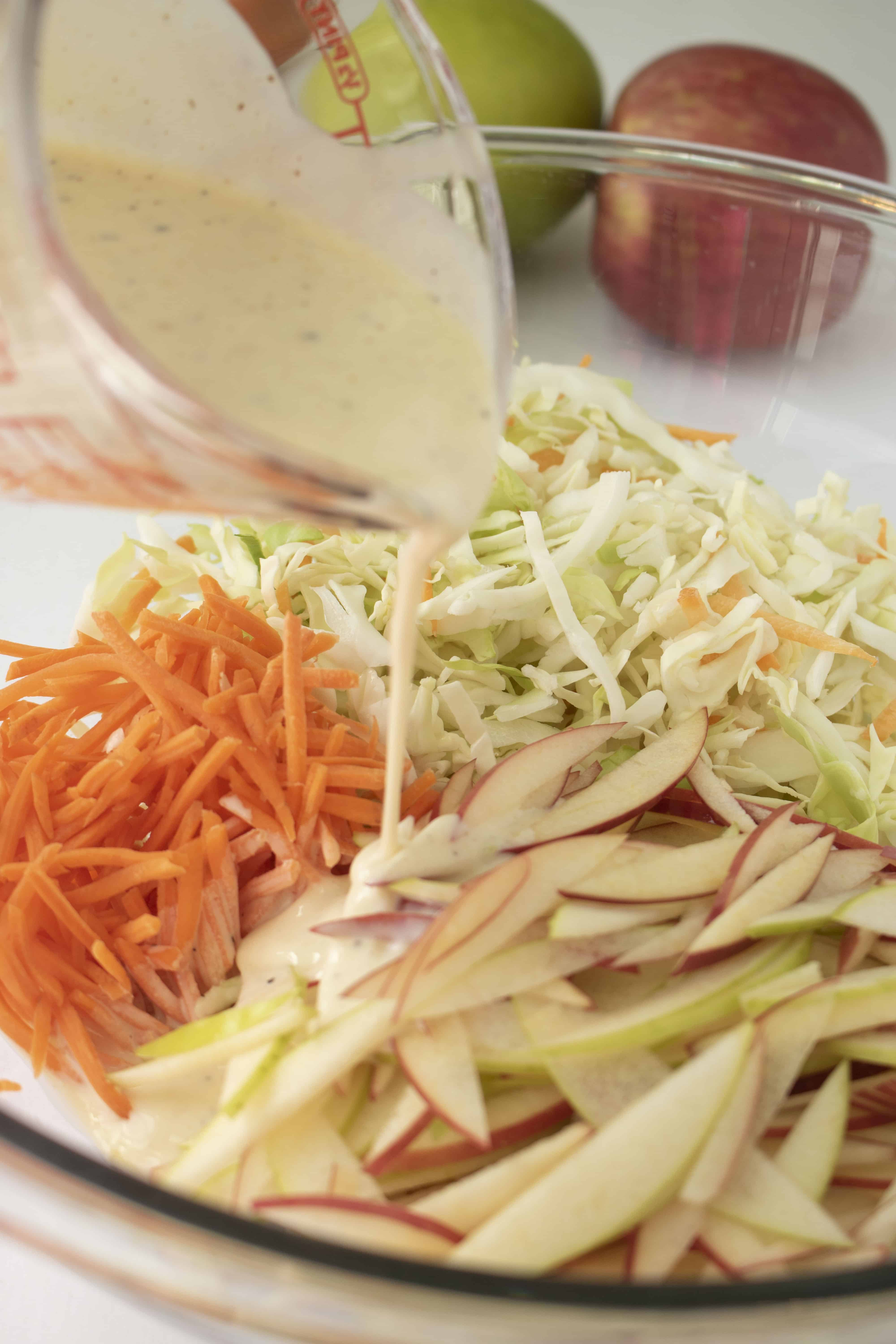 Dressing being pored onto slaw ingedients