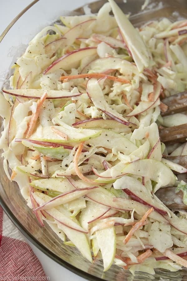 Apple slaw in a clear bowl on a white background