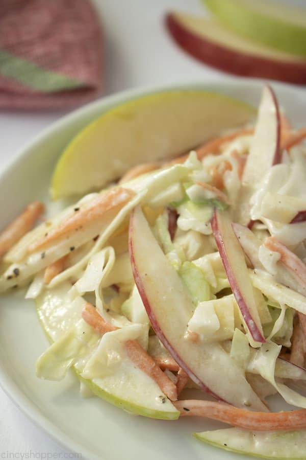 Serving of apple coleslaw on a white plate with napkin and wedges in background