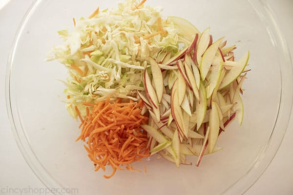 apple coleslaw ingredients in a clear bowl