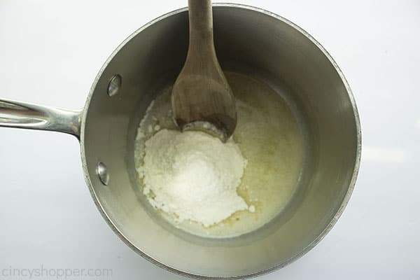 Flour added to melted butter with wooden spoon.
