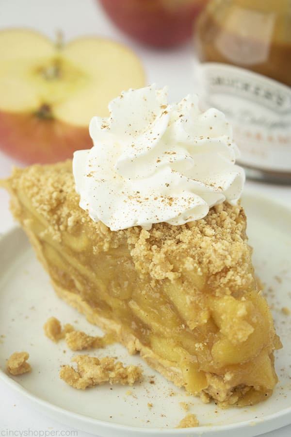 Slice of no bake apple pie with whipped cream on a white plate. Apple slices and caramel topping in backgroud.