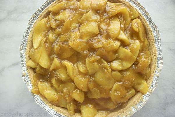 Cooked apples in graham cracker crust.