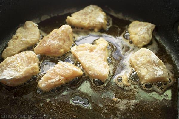 chicken frying in a dark pan