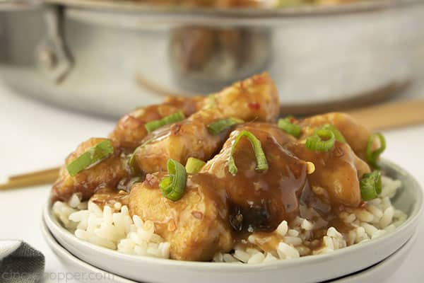 Homemade Chinese chicken over rice on a white plate and pan in background