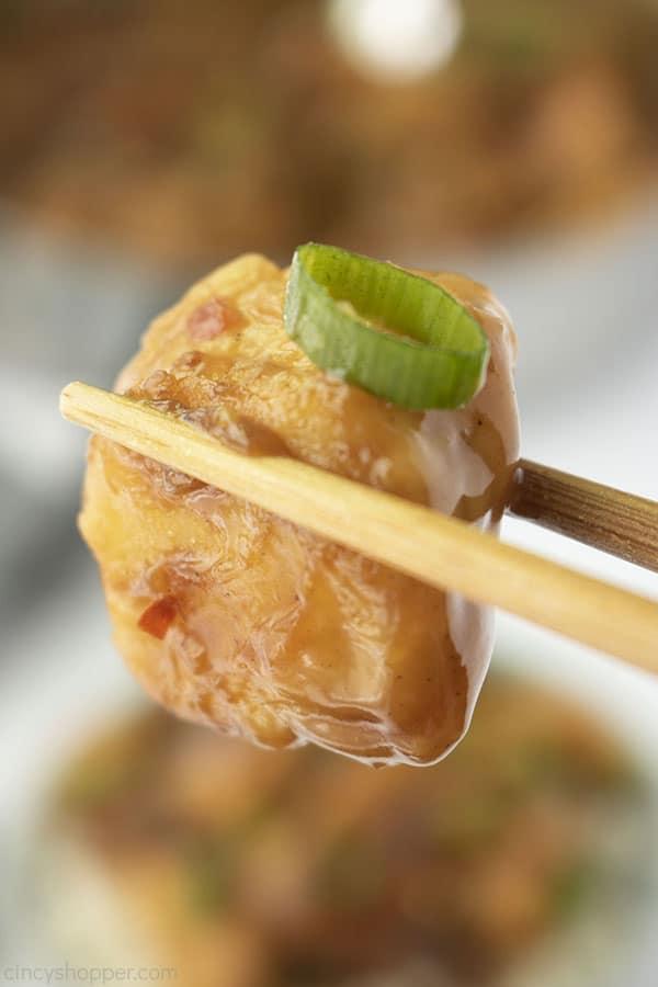 Chicken closeup between chopsticks.
