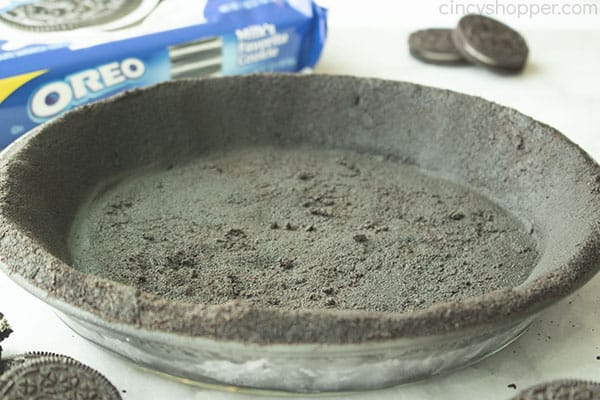 No Bake Oreo cookie crust in pie dish. Oreo cookie package and loose cookies in the white background.