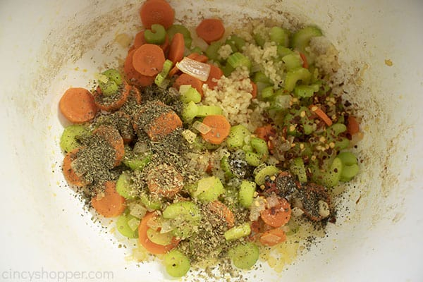 Spices added to vegetables in a white pot