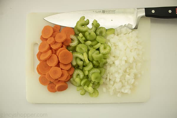 Chopped carrots, celery and onions on a white cutting board with a knife