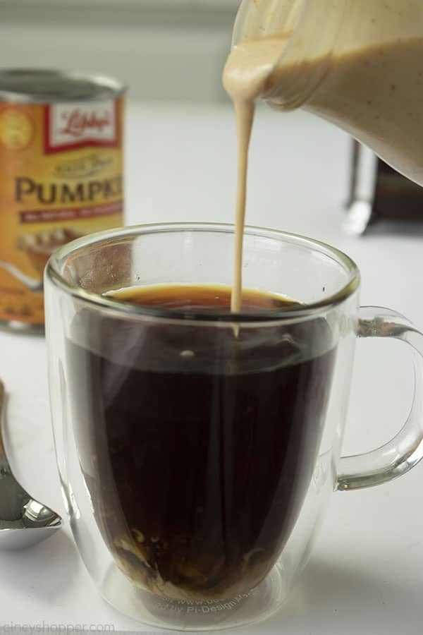 Clear coffee mug with homemade pumpkin creamer being poured in. White background with canned pumpkin in the distance.
