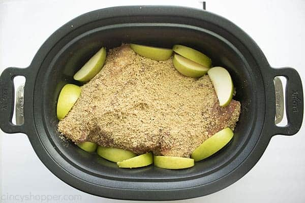 Overhead image of the Pulled Pork in a black oval Slow Cooker topped with the apple crisp rub and sliced green apples