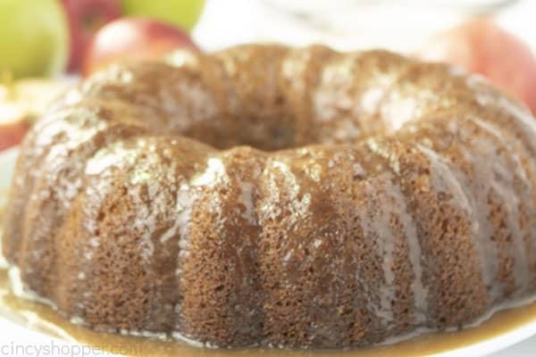 Glazed apple cake on a white plate.