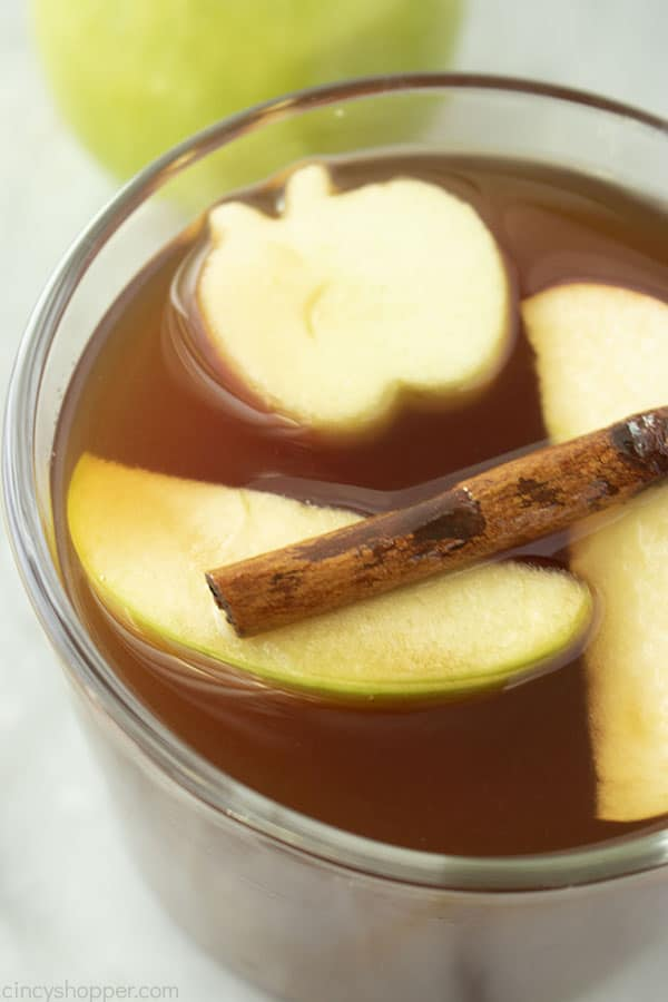 Clear mug with apple cider and floating fruit
