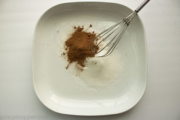 Cinnamon suagr mixture ina white bowl with whisk