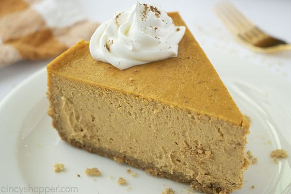 Slice of Pumpkin Cheesecake with whipped cream on a plate