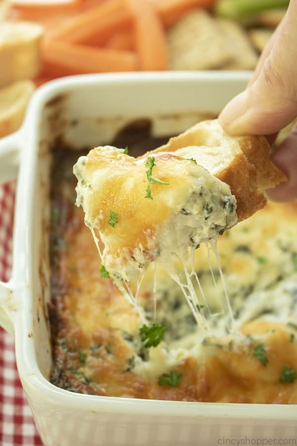 Hand dipping Cheesy Spinach Dip on bread