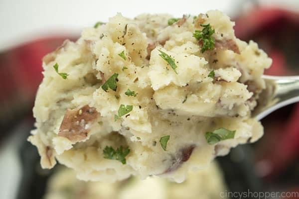 Finished mashed potatoes with butter and parsley on a spoon
