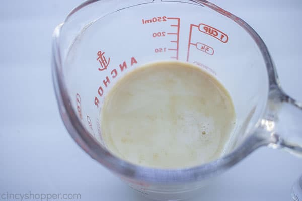 Vanilla added to milk in a measuring cup