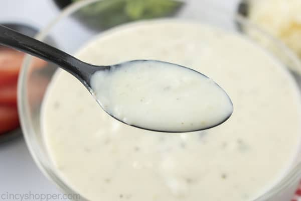 Spoon with white sauce for pizza