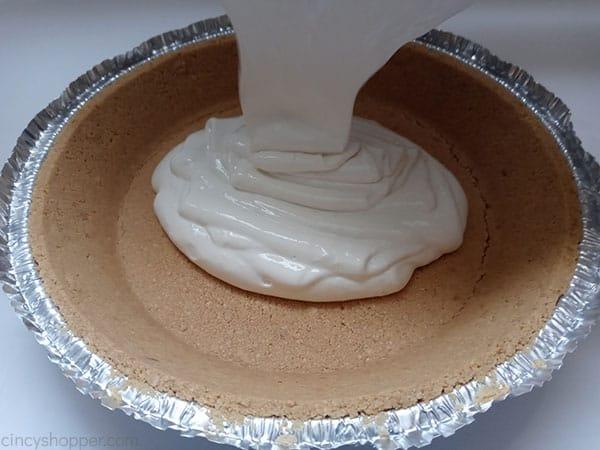 Poring lemonade pie mix into crust