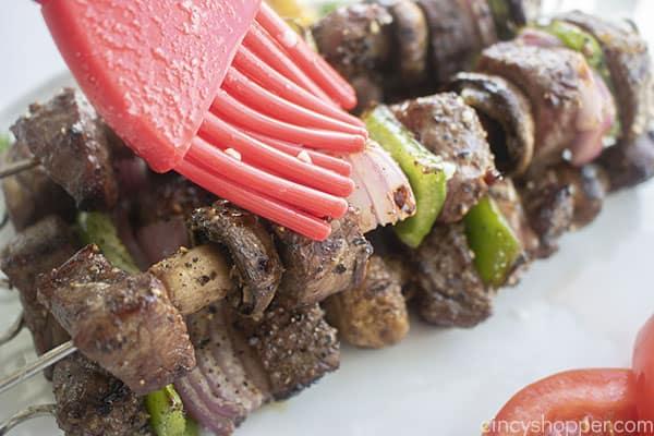 Brushing garlic butter on grilled Steak Kebabs