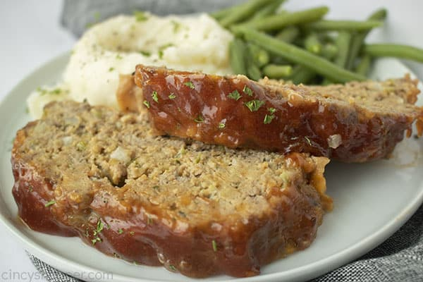 Copycat Cracker Barrel Meatloaf on a plate with mashed potatoes green beans